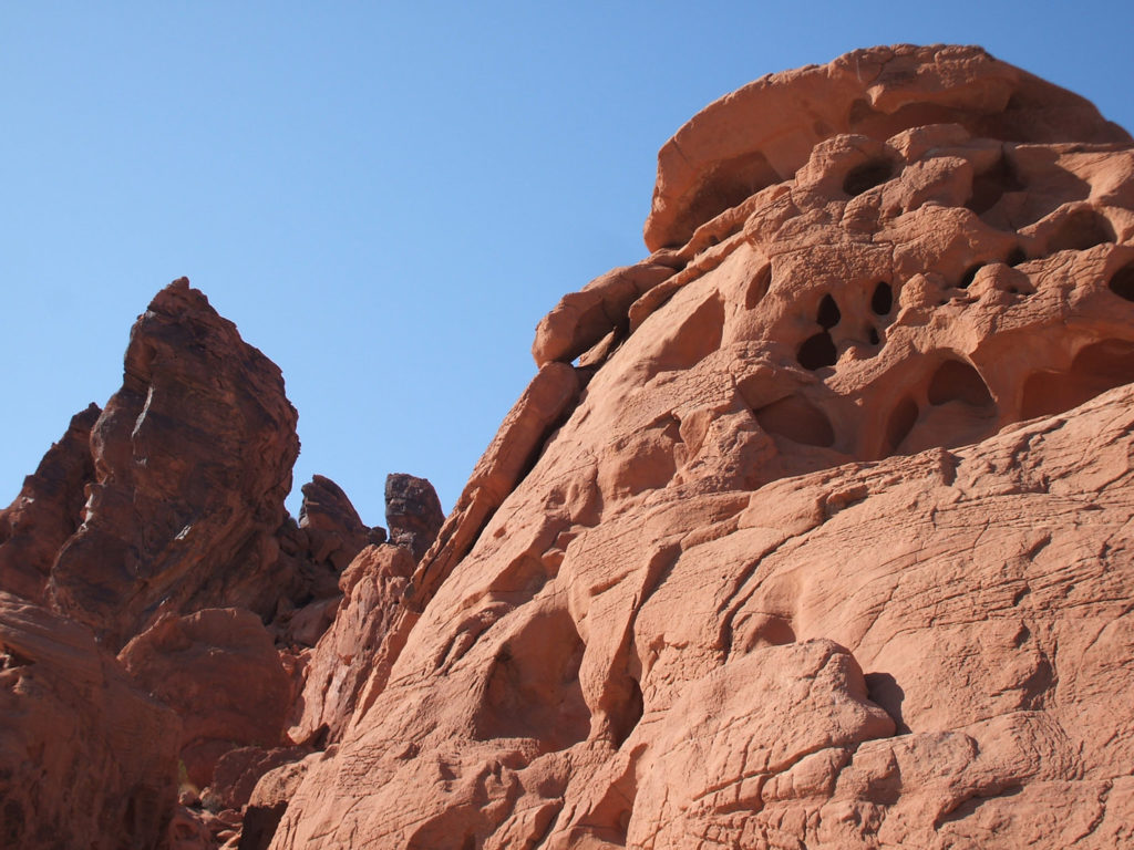 Orange and rust coloured rock formations against a clear blue sky at the Valley of Fire State Park, Nevada