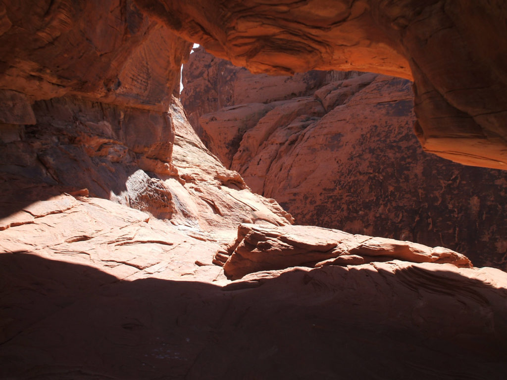Looking out into red and orange shadows from beneath an overhang of rocks in the Valley of Fire State Park, Nevada