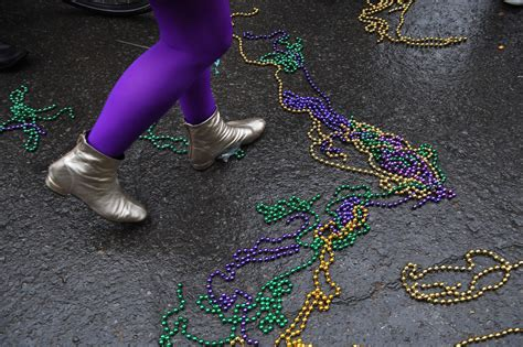 Person wearing purple tights and gold ankle booties walking along pavement littered with discarded chains of colourful Mardi Gras beads