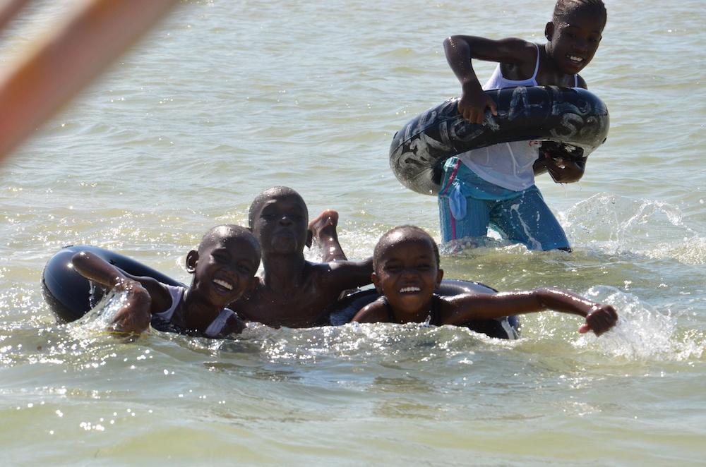 Four boys having fun splashing with inner tubes at the beach